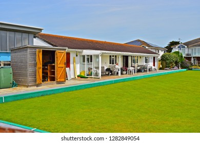 Milford on Sea, Hampshire / England - 6/24/2018: Milford on Sea Bowls Clubhouse in the Summer sunshine viewed here from the public footpath alongside the beach. The building overlooks the green.