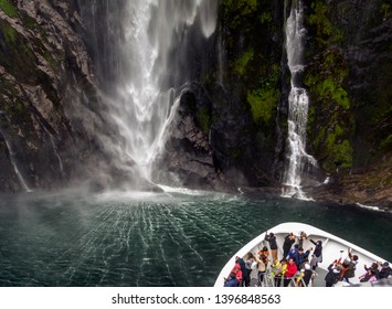 MILFORD SOUND, NEW ZEALAND - MARCH 04, 2019: South Island. Milford Sound fjord. Ship with tourists at the foot of the Stirling Falls (the greatest waterfalls at this fjord)