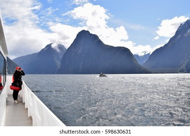 Milford Sound, New Zealand - October 15th, 2015 : The Milford Sound Cruise ship is approaching the Stirling Fall, which can be seen in the background afar.