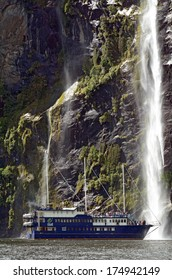MILFORD SOUND,NZ - JAN 14:Visitors sail in Milford Sound on a cruise boat close to a tall waterfall on Jan 14 2014.It's New Zealand's most famous tourist destination.