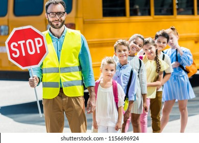 miling traffic guard with scholars looking at camera in front of school bus
