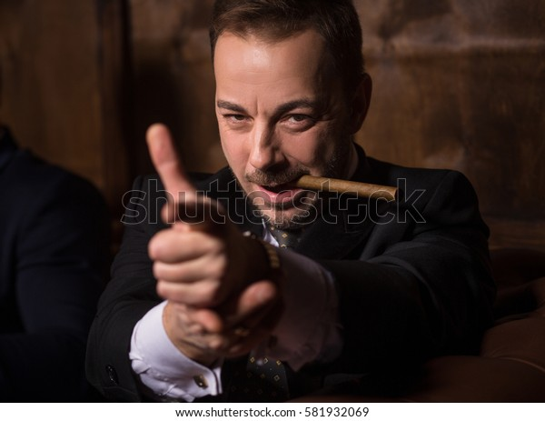 Militant businessman ready to strike. Handsome man spending time in men's club. Man smoking cigar and looking at camera.