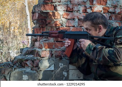 military aim at the target, hiding behind cover. soldier on brick wall background leads the fighting.preparing for battle. shooting from a Kalashnikov assault rifle. AKS-74