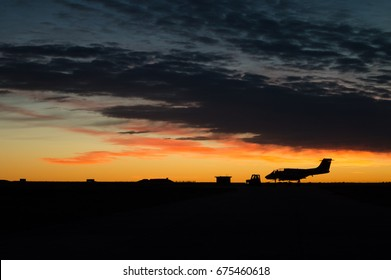 Military airplane silhouette beeing towed during sunrise. yellow sky