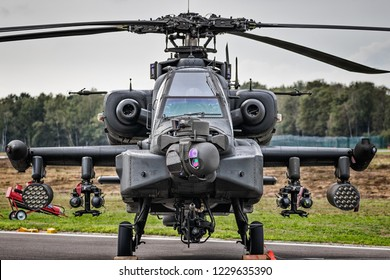 Military attack helicopter on the tarmac of an air base.