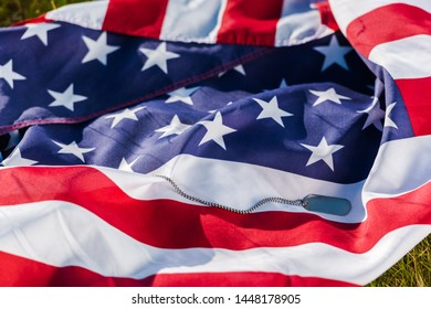 military badge on chain near american flag with stars and stripes