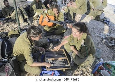 MILITARY BASE, ISRAEL - JUNE 17, 2015: Female soldiers playing backgammon. Soldiers having fun during a break from military training. Female Israeli soldier playing the guitar in the background.