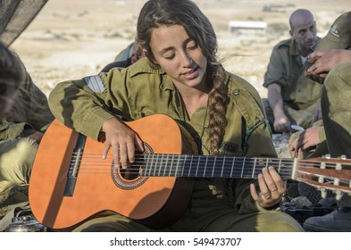 MILITARY BASE, ISRAEL - JUNE 17, 2015: Young female Israeli army soldier playing the guitar during break from military training. Female soldier relaxing by playing music on the guitar and singing.