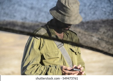 MILITARY BASE, ISRAEL - JUNE 17, 2015: Israeli army combat soldier looking at his phone. Officer texting on his smartphone while face is concealed behind a curtain. Soldier checking mobile phone.
