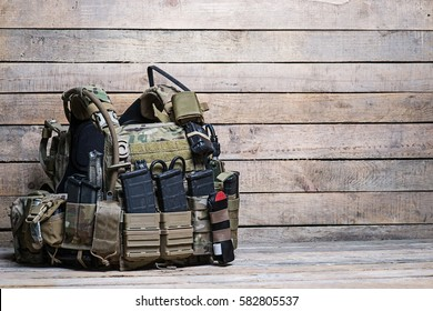 Military body armor,ammunition and ammo,radio and first aid tourniquet.On wooden table/Army bulletproof vest