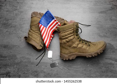 Military boots, USA flag and dog tags on grey background