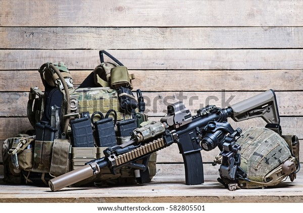 Military bulletproof vest,assult rifle,helmet with night-vision device on wooden background/Rifle,flak jacket and helmet