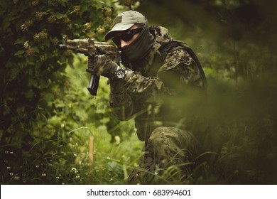 Military in camouflage among trees