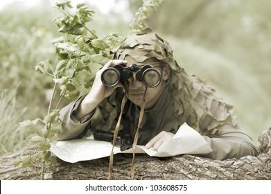 Military Camouflaged man in forest with black handgun and binocular