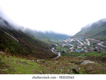 Military Camps and houses among thick smog in the valley in Gangtok, Sikkim, sky view.