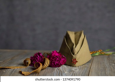 Military cap, carnations, Saint George ribbon on a wooden surface. Closeup