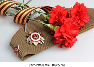 Military cap with order of Great Patriotic war and red flowers tied by Saint George ribbon