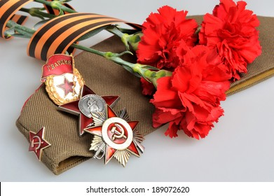 Military cap with red flowers, Saint George ribbon and orders of Great Patriotic war on gray