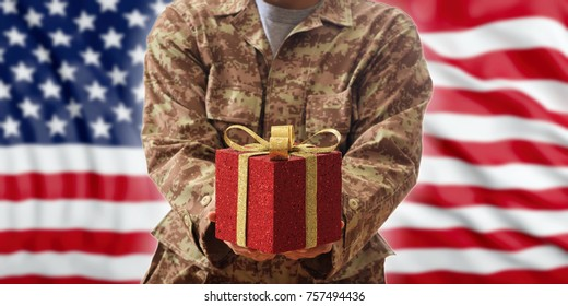 Military Christmas, Veterans gift box. American soldier offering a red package on US flag background