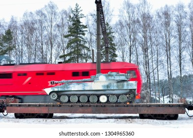 Military combat Soviet tank, artillery tracked vehicle on a railway cargo platform amid a passing red passenger train at high speed