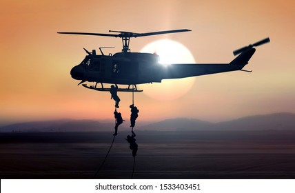 Military commandos helicopter drops during sunrise