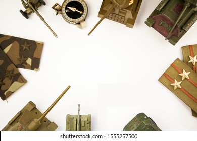 Military concept. Background with old military compass, military chevrons and miniature toy tanks on white background, free space for text in the center, without people. Flat lay