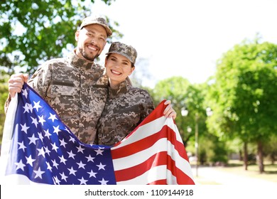 Military couple with American flag in park