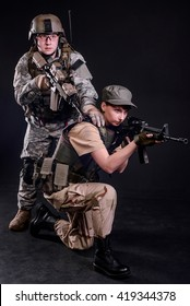Military Couple In Uniform with guns on dark background/Military couple with guns