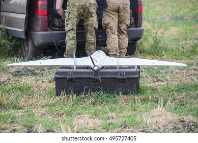 Military drone with propeller on army box on  background of male legs in uniform/Military drone on black box