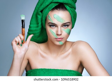 Military facial cream. Serious woman holding up brush. Photo of woman in green towels with flawless skin on blue background. Beauty & Skin care concept