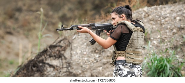Military female soldiers in action tactical combat shooting from rifle machine gun. Shooting and weapons. Outdoor shooting range