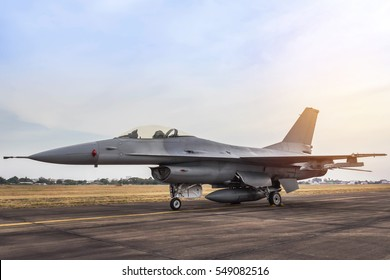 military fighter jet aircraft parked on runway in sunset