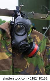 military gasmask hanging over an uniform