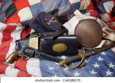 Military gear from the Civil War used by Union Cavalry who fought for the North, the United States. A flag is draped with a war time patriotic quilt, bag, canteen, hat, pistol, saber, belt and buckle.