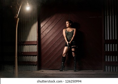 Military girl with a gun in a desserted area