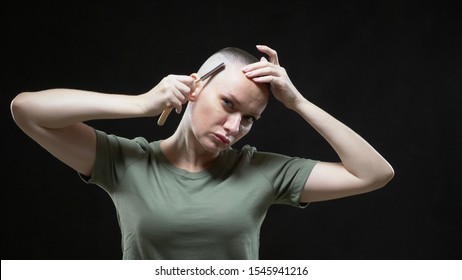 Military girl in a T-shirt shaves her head with a dangerous razor on a black background