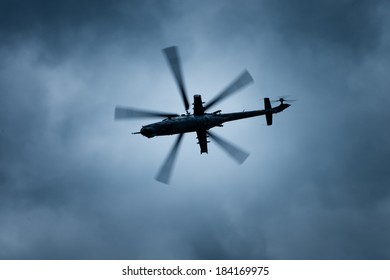 Military gunship helicopter on the stormy sky.