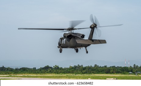 military helicopter flying overhead on a clear day , rotary wing aircraft, , up in the sky.