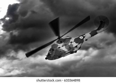 Military helicopter landing. Dramatic stormy sky.