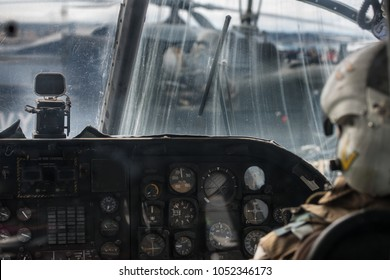 Military helicopter pilot operate in navy aircraft cabin at army base
