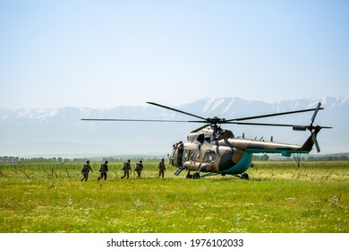 Military helicopter with soldiers. Armed conflict in Afghanistan, fighting. Soldiers in camouflage clothing goes to a military helicopter. Air armament, parachutist.