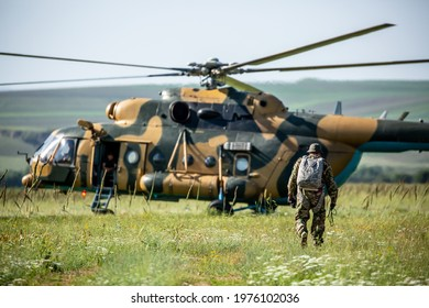 Military helicopter with soldiers. Armed conflict between Afghanistan, military action. A soldier in camouflage clothing walks towards a military helicopter. Air armament, parachutist.