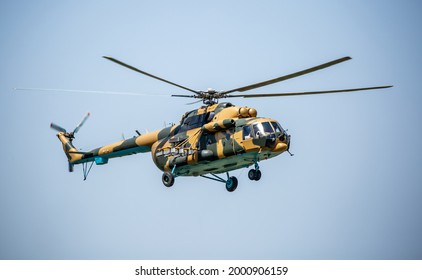 A military helicopter with soldiers flies in the sky. Armed conflict, military action. Air armament and territory protection. Armed conflict in Afghanistan.