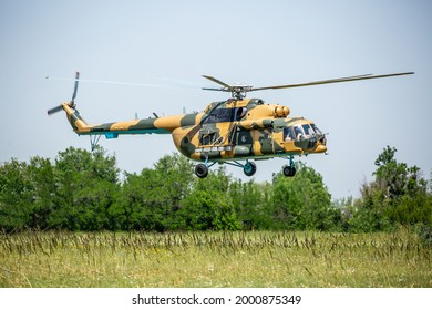 A military helicopter with soldiers takes off over the field. Armed conflict, military action. Air armament and territory protection.