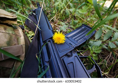 Military helmet, rifle and a flower in the grass. Soldier, military, stop war, strike ball  concept