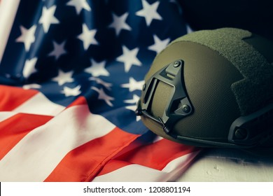 Military helmets and American flag on background