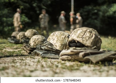 Military helmets and bulletproof vests are lined up on the grass.