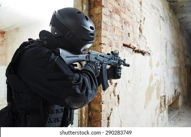 Military industry. Special forces or anti-terrorist police soldier,  private military contractor armed with assault rifle ready to attack during clean-up operation, mission