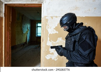 Military industry. Special forces or anti-terrorist police soldier,  private military contractor armed with pistol during clean-up operation, mission
