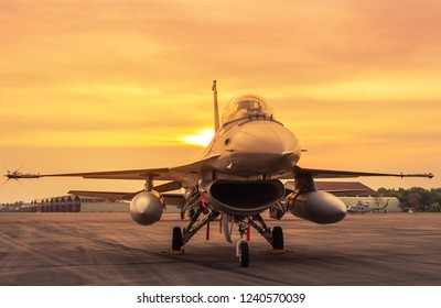 military jet aircraft parked on runway in sunset